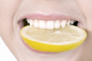 Smiling, biting lemon slice Dr. Joe Thomas Dentistry