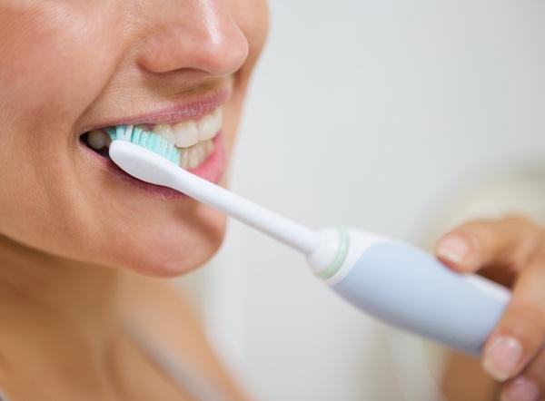 closeup of woman brushing teeth Dr. Joe Thomas Dentistry