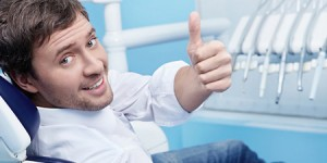 man in dental chair smiling with thumb up Dr. Joe Thomas Dentistry