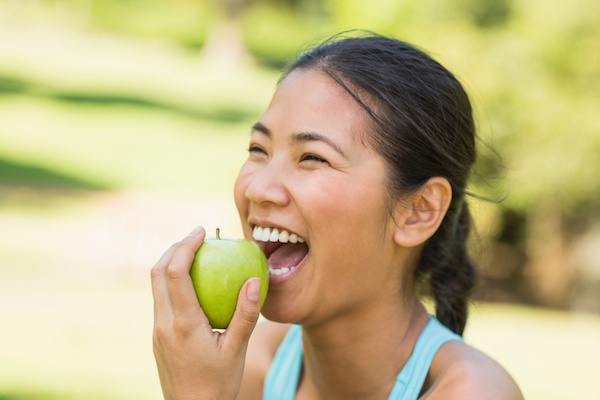 Happy woman eating an apple outside Dr. Joe Thomas Dentistry
