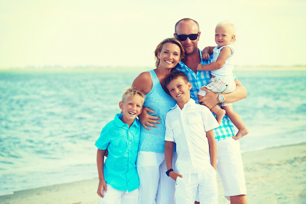 Family smiling on beach, family photo