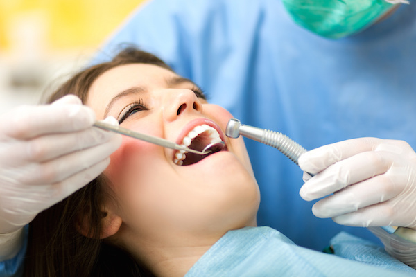 Dentist performing a screening on female patient